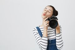 Trendy girl holding photo camera in hands, smiling happily at camera, taking photos, pouting lips. Brunette photographer. Trendy girl holding photo camera in Stock Photo