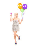 Trendy girl holding a pink cocktail and balloons Royalty Free Stock Photos