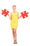 Trendy girl holding two pieces of a puzzle Royalty Free Stock Photography