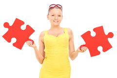 Trendy girl holding two pieces of puzzle Royalty Free Stock Images