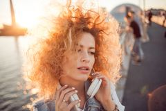 Trendy girl with large headphones on a city walk, close up. Portrait of a young charming blonde with lush curls, music lover on the street stock photos