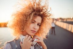 Trendy girl with large headphones on a city walk, close up. Portrait of a young charming blonde with lush curls, music lover on the street Stock Photo