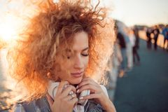 Trendy girl with large headphones on a city walk, close up. Portrait of a young charming blonde with lush curls, Enjoy the music and closed eyes royalty free stock images