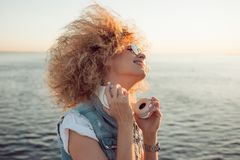 Trendy girl with large headphones and sunglasses on a city walk, close up. Portrait of a young charming blonde with lush curls, music lover on the sea stock photo