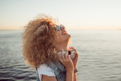 Trendy girl with large headphones and sunglasses on a city walk, close up. Portrait of a young charming blonde with lush curls, music lover on the sea royalty free stock image