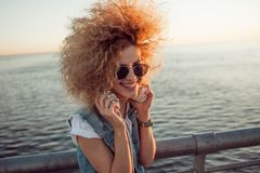 Trendy girl with large headphones and sunglasses on a city walk, close up. Portrait of a young charming blonde with lush curls, music lover on the sea stock image