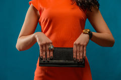 Trendy girl near blue background Stylish red dress and clutch. Royalty Free Stock Photography