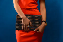 Trendy girl near blue background Stylish red dress and clutch. Stock Photography