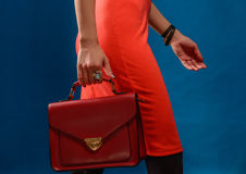 Trendy girl near blue background Stylish red dress and clutch. Royalty Free Stock Photos