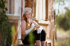 Trendy girl outside house. Trendy young girl in hat sat outside rural house in summer Royalty Free Stock Photo