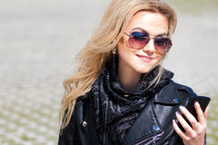 Trendy girl portrait outdoor. A walk in the city. Young woman uses phone Royalty Free Stock Images