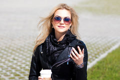 Trendy girl portrait outdoor. A walk in the city. Young woman uses phone and drinking coffee Stock Images