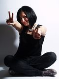 Trendy girl showing the victory sign. A portrait about an attractive trendy girl with black hair who is showing the victory sign with two hands and she has a Stock Image