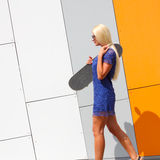 Trendy girl with skateboard. Against the background of an orange colored wall. Skateboarding. Outdoors, lifestyle Stock Photos