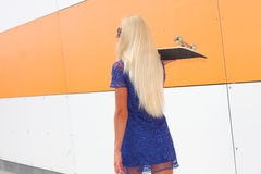 Trendy girl with skateboard. Against the background of an orange colored wall. Skateboarding. Outdoors, lifestyle Royalty Free Stock Photo