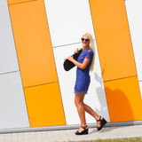 Trendy girl with skateboard. Against the background of an orange colored wall. Skateboarding. Outdoors, lifestyle Royalty Free Stock Image