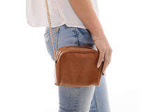 Trendy girl with small brown leather bag handbag in hand Royalty Free Stock Image