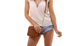 Trendy girl with small brown leather bag handbag in hand Royalty Free Stock Photos