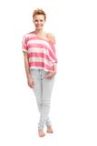 Trendy girl in t-shirt and jeans. Trendy young woman standing barefoot in t-shirt and jenas, smiling Royalty Free Stock Photo
