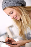 Trendy girl taking notes on smartphone Stock Images
