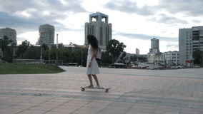 Trendy girl taking selfie while riding longboard. Side view of young woman in dress and sneakers riding longboard and taking selfie with camera stock video