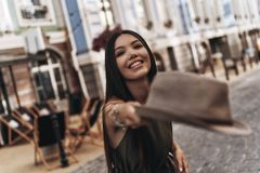 Trendy girl. Attractive young woman throwing a hat and smiling while standing outdoors Stock Photos