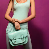 Trendy girl with a turquoise bag  on  purple background. Trendy girl with a turquoise bag and T-shirt on a purple background Royalty Free Stock Photography