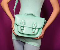 Trendy girl with a turquoise bag  on  purple background. Trendy girl with a turquoise bag and T-shirt on a purple background Stock Photo