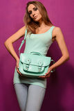 Trendy girl with a turquoise bag  on  purple background Royalty Free Stock Photos