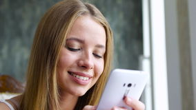 Trendy girl typing message on smartphone stock footage