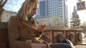 Trendy girl using smartphone on city street at sunset, relax, enjoy sun and wind. Trendy blonde girl using smartphone on city street at sunset, relax, enjoy sun stock video