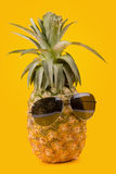 Trendy glasses summer pineapple wearing hipster style on yellow. Background Stock Photography