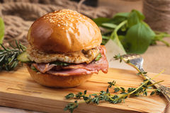 Trendy glossy breakfast burger with ham and eggs. Concept: restaurant menus, healthy eating, homemade, gourmands, gluttony. Trendy glossy breakfast burger with Royalty Free Stock Images