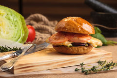 Trendy glossy breakfast burger with ham and eggs. Concept: restaurant menus, healthy eating, homemade, gourmands, gluttony. Trendy glossy breakfast burger with Stock Photography