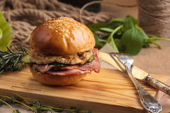 Trendy glossy breakfast burger with ham and eggs. Concept: restaurant menus, healthy eating, homemade, gourmands, gluttony. Trendy glossy breakfast burger with Royalty Free Stock Photo