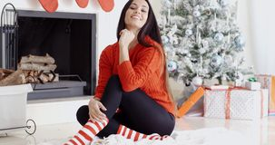Trendy gorgeous young woman relaxing at Xmas. Sitting on a rug on the floor in front of the Christmas tree grinning at the camera stock video footage