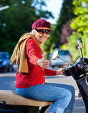 Trendy grandmother riding a scooter Stock Photo