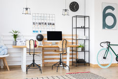 Open workspace connected with hall. Trendy green and blue bicycle standing against a white wall in hall connected with open workspace Royalty Free Stock Images