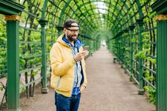 Trendy guy with beard and moustache wearing anorak, jeans and cap standing sideways having attentive look into his smartphone isol. Ated over green arch. Human stock image