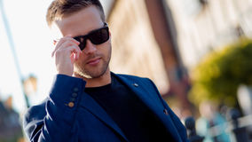 Trendy guy with glasses in the street. Portrait on the background of the city. Trendy guy with glasses in the street Stock Images