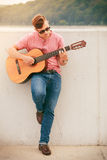 Trendy guy with guitar outdoor Stock Images