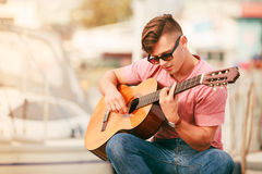 Trendy guy with guitar outdoor Royalty Free Stock Image