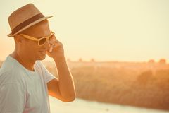 Modern guy with hat talking on mobile phone outdoors Royalty Free Stock Photography