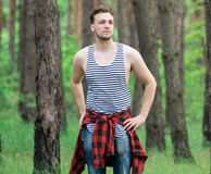 Trendy guy in the pine forest Royalty Free Stock Photos