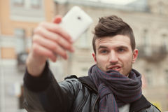 Trendy guy taking a selfie. On the street Royalty Free Stock Images