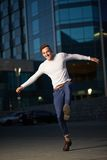 Trendy handsome guy jumping for joy. Against the evening city Royalty Free Stock Photos