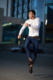 Trendy handsome guy jumping late for. An evening city background Stock Image