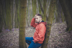 Trendy handsome man posing in spring park alone.  Royalty Free Stock Photography