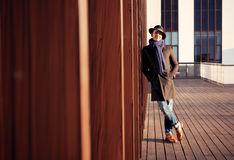 Trendy handsome young man in autumn fashion standing in urban environment. Stock Photography