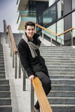 Trendy handsome young man in winter fashion standing on a long staircase Stock Photo